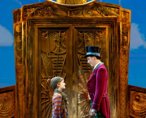 Henry Boshart as Charlie Bucket and Noah Weisberg as Willy Wonka. Roald Dahl's CHARLIE AND THE CHOCOLATE FACTORY. Photo by Joan Marcus.