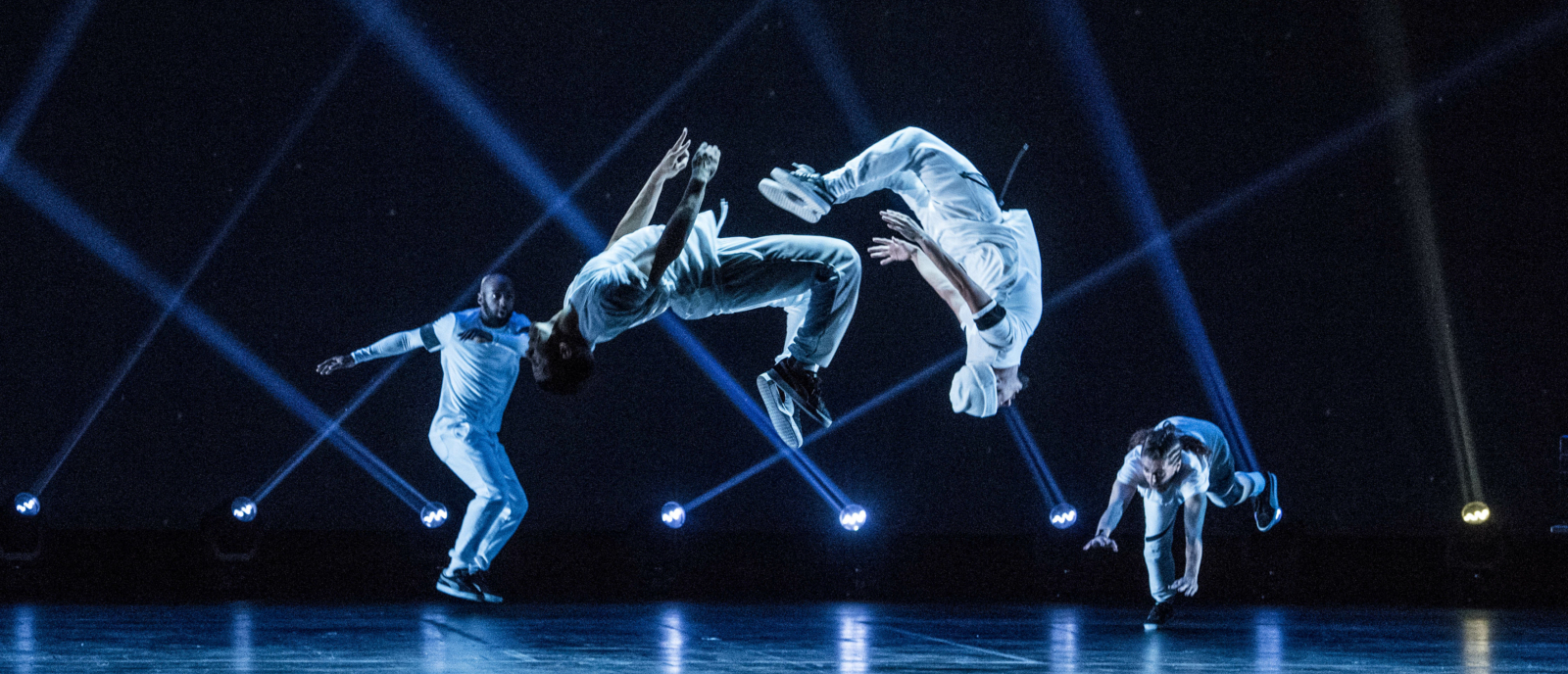 On a dark stage with blue lights, two dancers are doing backflips in the foreground while two more dancers watch on from the background
