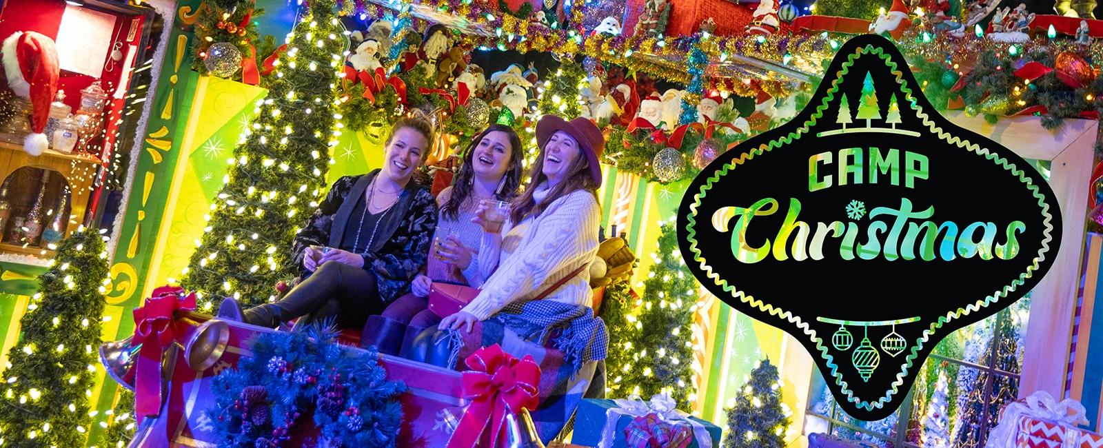 Three young women are in a sleigh surrounded by Christmas lights of all color, with a two dimensional black ornament overlaying the photo with the words Camp Christmas