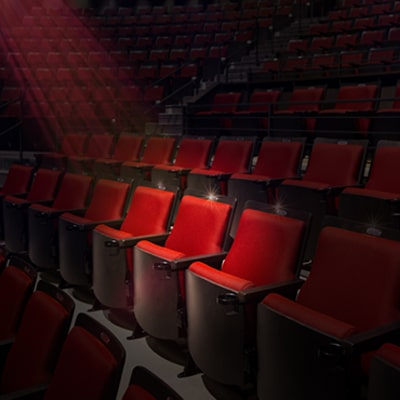 Empty red seats with a spotlight illuminating a single seat.