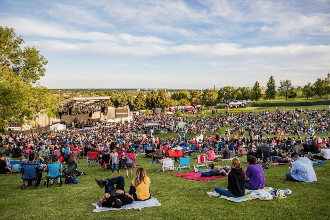 A crowd of people sitting on blankets in the grass, facing an amphitheatre in the distance, while the sky is blue with gentle clouds.